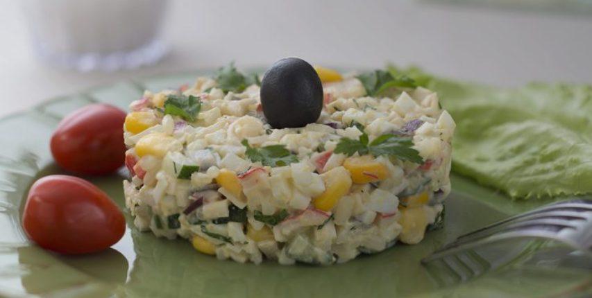Салат с рисом, крабовыми палочками, кукурузой, яйцами и огурцом